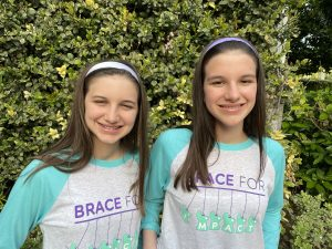 Hadley and Delany wearing Brace for Impact T's